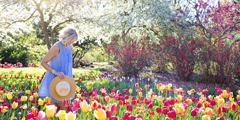 kvinna bland blommor - Hur blir man en lycklig människa